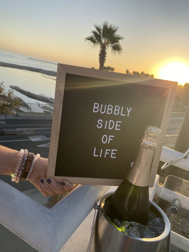 Letter board sign with Bubbly Side of Life in front of a beach view with champagne