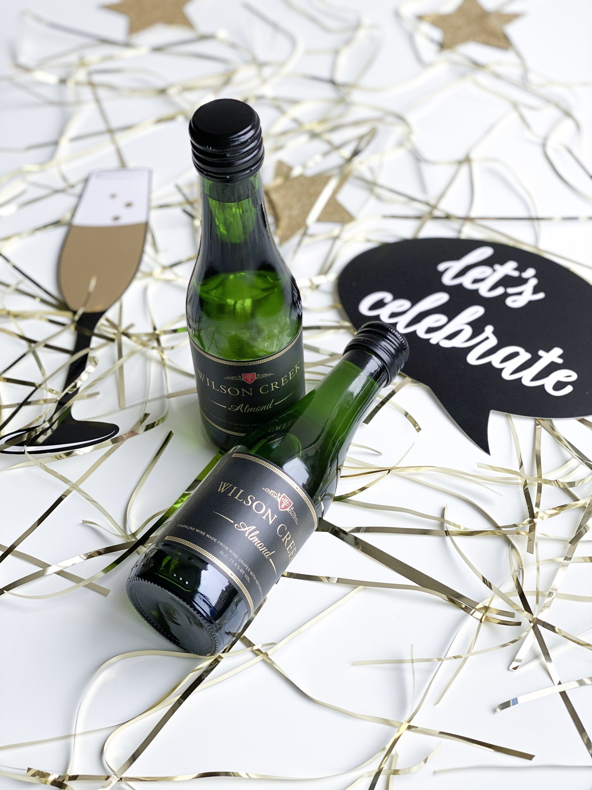Wilson Creek Winery 2 small Almond Sparkling Wine Bottles with gold confetti and a let's celebrate quote bubble